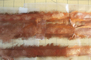 Place the three pieces of Red Artist Tape on wax paper and sponge paint it with copper paint.