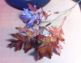 Attach the leaves to wire with black Artist Tape and twist every three pieces into stems.